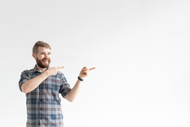 Szczęśliwy zabawny hipster młody człowiek z wąsem, pozowanie na białym tle i wskazując na prawo