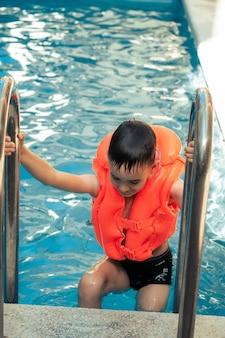 Szczęśliwy zachwycający dzieciak z mokrymi włosami stojący na chromowanej poręczy w słodkiej wodzie pływanie pomarańczowy basen na zewnątrz kamizelka ratunkowa w letni dzień wypoczynku. letnie zajęcia dla szczęśliwego dziecka na basenie