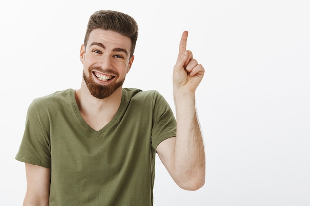 Szczęśliwy, zachwycony i beztroski, atrakcyjny dorosły mężczyzna z brodą, śmiejący się radośnie, świetnie się bawiąc wyglądając na zachwyconego i radosnego, wskazującego w górę lub pokazującego numer jeden na białej ścianie
