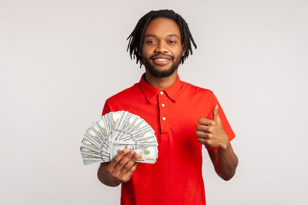 Szczęśliwy zadowolony człowiek trzyma banknoty dolarowe i pokazuje kciuk w górę, ciesząc się bogatym życiem.