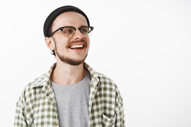 Szczęśliwy, zadowolony i zachwycony, szczęśliwy chłopiec na deskorolce w czarnych okularach beanie i codziennej koszuli w kratkę, wyglądający dobrze z szerokim, zadowolonym uśmiechem, słuchający kumpel opowiadający zabawną historię na szarej ścianie