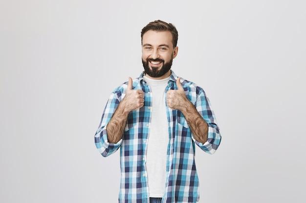 Szczęśliwy zadowolony klient męski pokazuje kciuki do góry i uśmiecha się