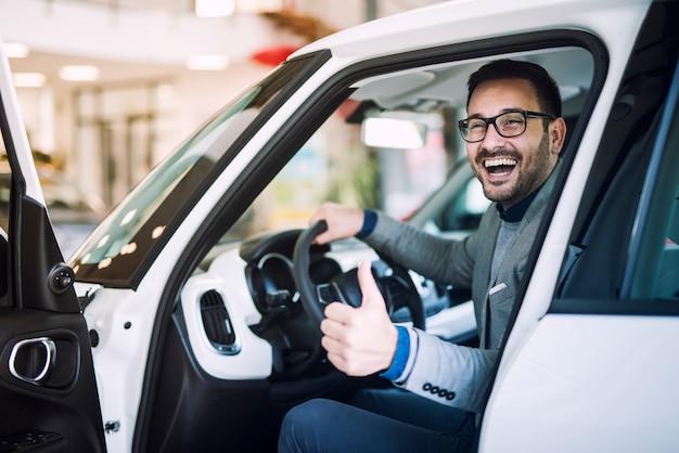Szczęśliwy zadowolony klient właśnie kupił nowy samochód w salonie samochodowym