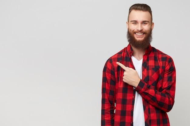 Szczęśliwy zadowolony młody brodaty facet w kraciastej koszuli radośnie uśmiechnięty, wskazując palcem wskazującym w lewo, na białym tle