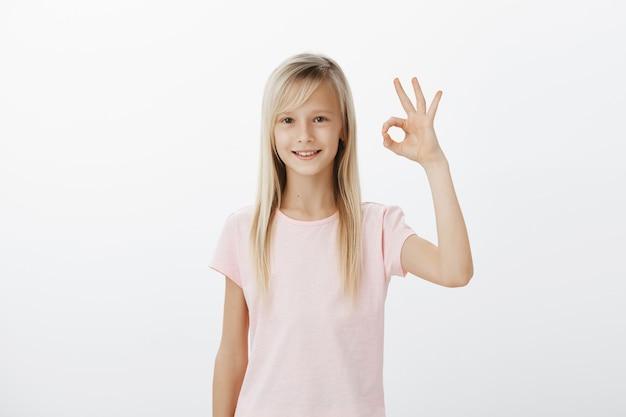 Szczęśliwy zadowolony młody dzieciak pokazuje dobry gest, zatwierdza lub poleca