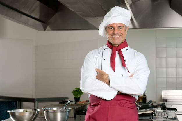 Szczęśliwy zadowolony szef kuchni patrząc na kamery i uśmiechając się w swojej restauracji