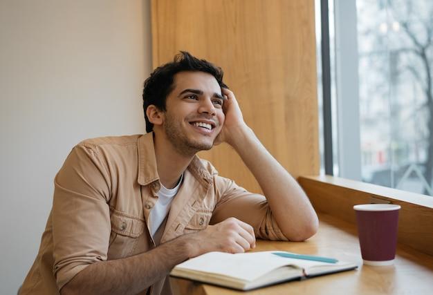 Szczęśliwy zadumany indyjski student studiujący, uczący się języka, szukający kreatywnego rozwiązania