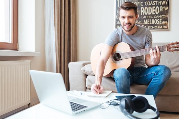 Szczęśliwy zainspirowany młody człowiek z laptopem grający na gitarze i piszący nową piosenkę w notatniku