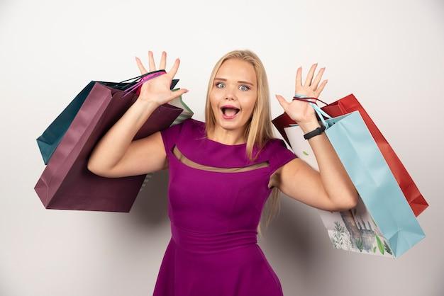 Szczęśliwy zakupoholiczka trzymając kolorowe torby na zakupy.