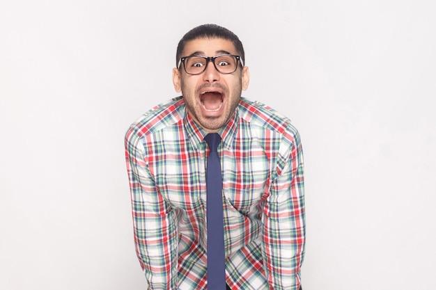 Szczęśliwy zaskoczony brodaty biznesmen w kolorowe kraciaste koszule, niebieski krawat i czarne okulary, stojąc i patrząc na kamery z zdziwioną twarzą i otwartymi ustami. strzał studio, na białym tle na szarym tle