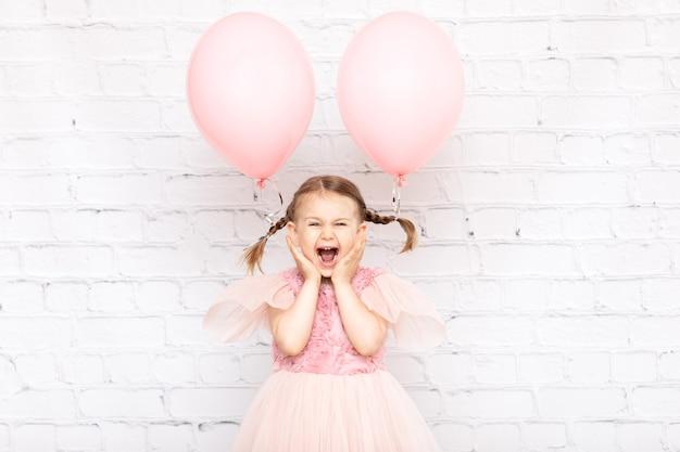 Szczęśliwy zaskoczony emocja zabawne dziecko z pastelowymi różowymi balonami na imprezie urodzinowej makieta