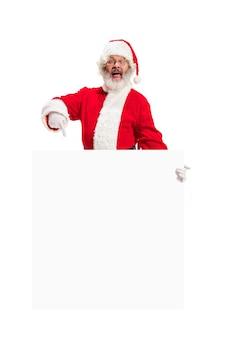 Szczęśliwy zaskoczony święty mikołaj, wskazując na pustą reklamę