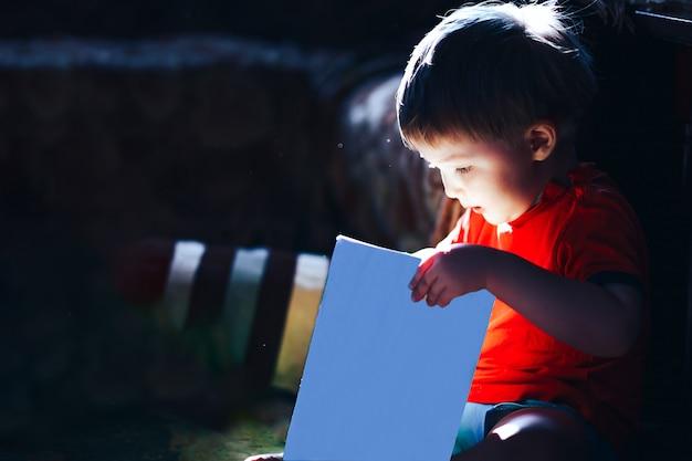 Szczęśliwy zaskoczony trzy lata chłopiec czytanie książki magii bajki, światło pochodzi z książki, na białym tle książki