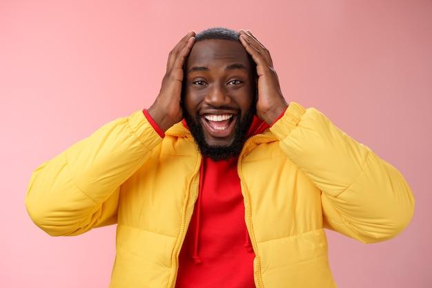 Szczęśliwy zaskoczony zadowolony młody afroamerykanin młoda kurtka czerwona bluza z kapturem uśmiech rozbawiony zdumiony...
