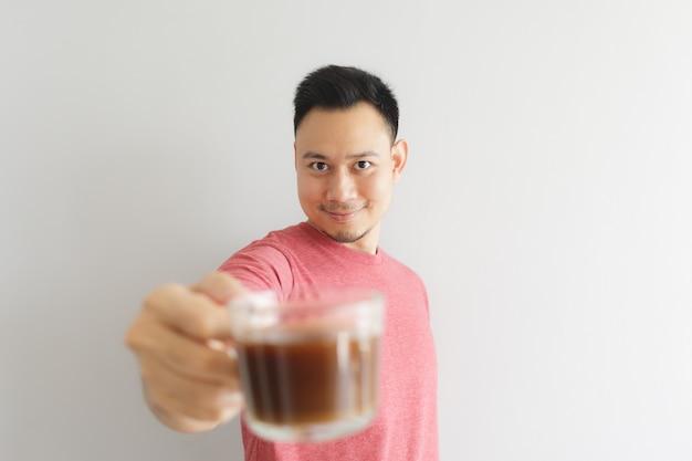 Szczęśliwy zdrowy człowiek w czerwony t-shirt pije kawę lub pić ziół azjatyckich.