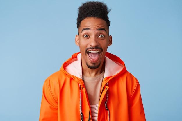 Szczęśliwy zdumiony, atrakcyjny, ciemnoskóry afroamerykanin chłopiec ubrany w pomarańczowy płaszcz przeciwdeszczowy, z szeroko otwartymi ustami, uśmiecha się szeroko