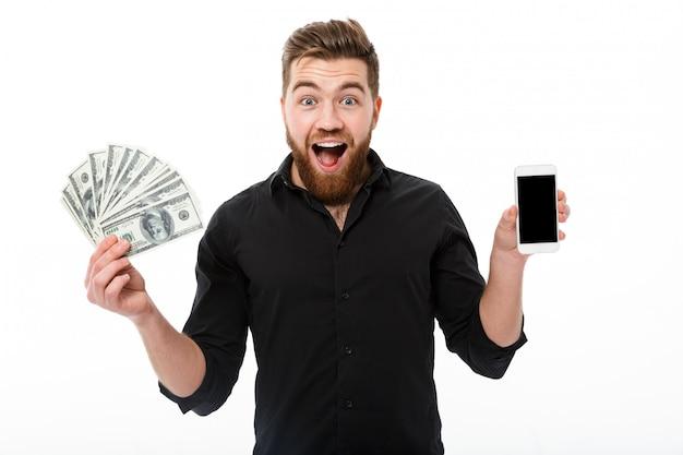 Szczęśliwy zdziwiony brodaty biznesowy mężczyzna w koszulowym mienie pieniądze