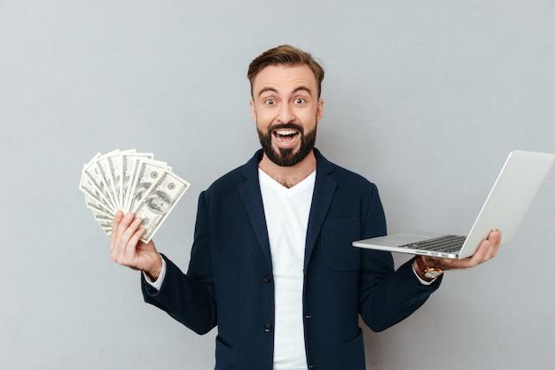 Szczęśliwy zdziwiony brodaty mężczyzna w biznesowym odzieżowym mieniu pieniądze i laptopie podczas gdy patrzejący kamerę nad popielatym