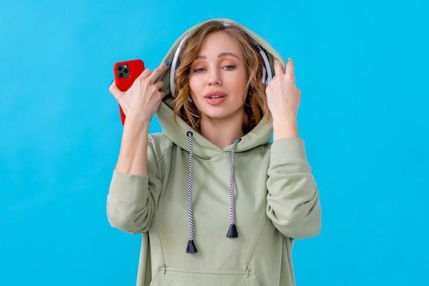 Szczęśliwy zęby uśmiech kobieta słuchać muzyki słuchawki trzymając smartfon w ręku patrząc kamery kaukaski kobieta cieszyć się podcast lub książki audio ubrany oversize bluza z kapturem niebieskie tło bliska portret