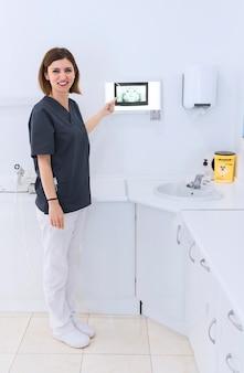 Szczęśliwy żeński dentysta wskazuje przy zębu promieniowaniem rentgenowskim w klinice