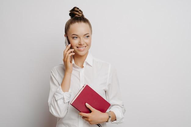 Szczęśliwy żeński dyrektor w białej koszuli z klasyczną fryzurą weryfikujący informacje finansowe w notatniku ze swoim partnerem, rozmawiający przez telefon komórkowy i uśmiechający się stojąc na jasnym tle