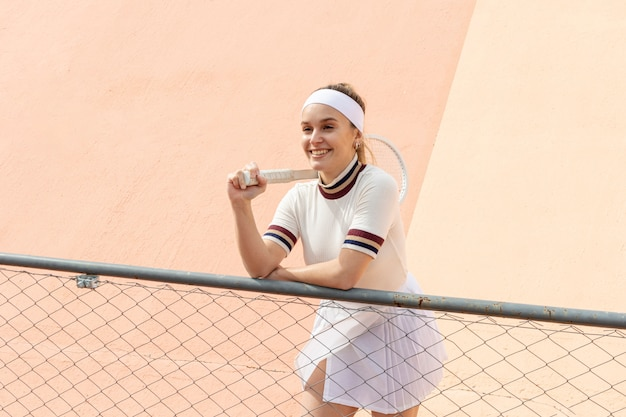 Szczęśliwy żeński gracz w tenisa z kantem