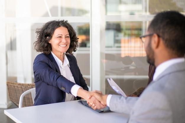 Szczęśliwy żeński klient dziękuje konsultantowi za pomoc