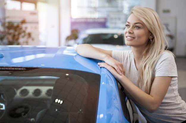 Szczęśliwy żeński klient opiera na jej nowym samochodzie ono uśmiecha się patrzejący daleko od sennie