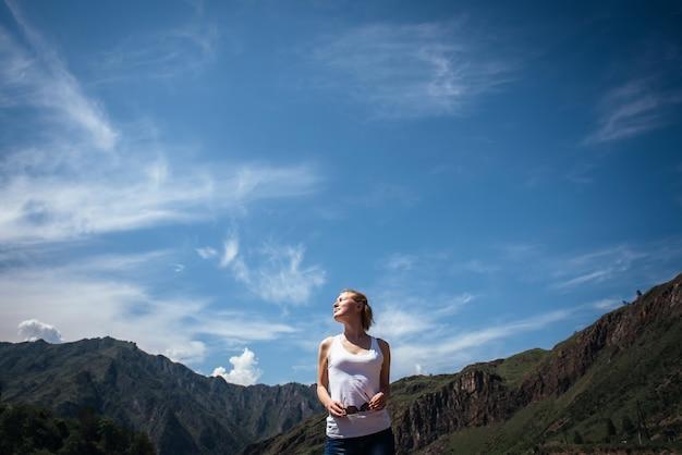 Szczęśliwy żeński podróżnik w białej koszulce przeciw pięknym górom i niebieskiemu niebu na słonecznym dniu.
