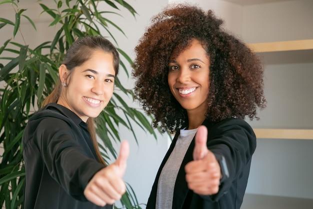 Szczęśliwy żeński pracownicy biurowi kciuki do góry i uśmiechnięte. dwóch wesołych profesjonalnych przedsiębiorców stojących razem i pozujących w sali konferencyjnej. koncepcja pracy zespołowej, biznesu, sukcesu i współpracy