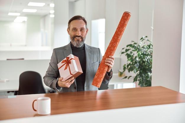 Szczęśliwy żeński pracownik biurowy uśmiecha się i trzyma papier pakowy i teraźniejszość