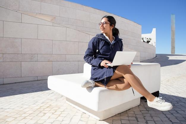 Szczęśliwy żeński uczeń siedzi na ławce i używa laptop outdoors