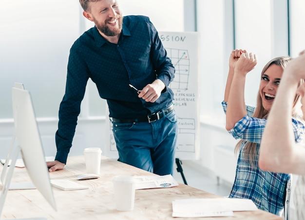 Szczęśliwy zespół biznesowy na spotkaniu roboczym w biurze