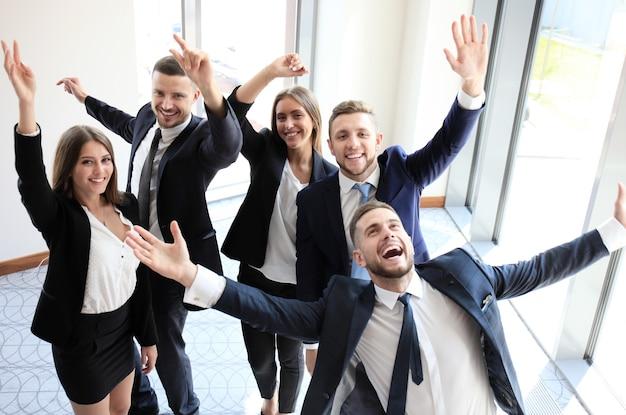 Szczęśliwy zespół biznesowy świętujący zwycięstwo w biurze