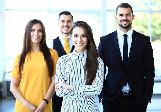 Szczęśliwy zespół biznesowy z rękami skrzyżowanymi w biurze