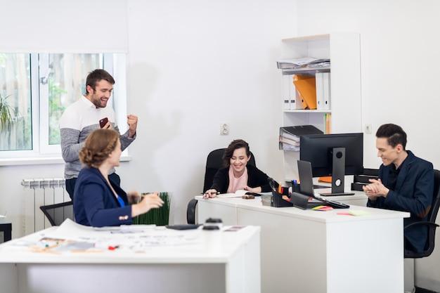 Szczęśliwy zespół, który właśnie otrzymał wspaniałe wiadomości przez telefon, wiwatując w biurze