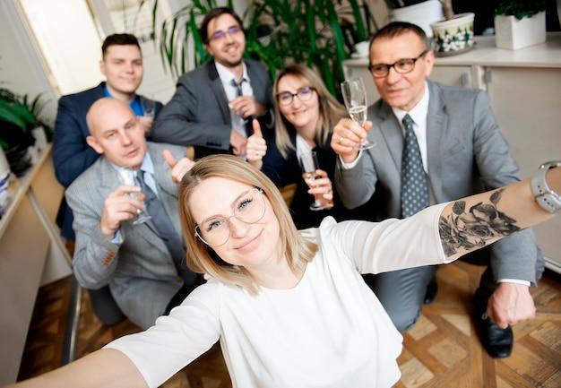 Szczęśliwy zespół ludzi biznesu z kieliszkami do szampana, biorąc selfie na spotkanie biznesowe