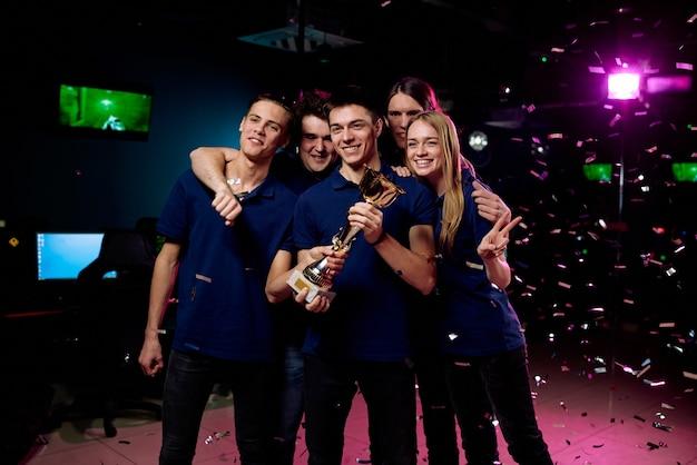 Szczęśliwy zespół młodych graczy komputerowych wygrywających złoty puchar cybersports w konkursie i pozujących do zdjęcia grupowego pod konfetti