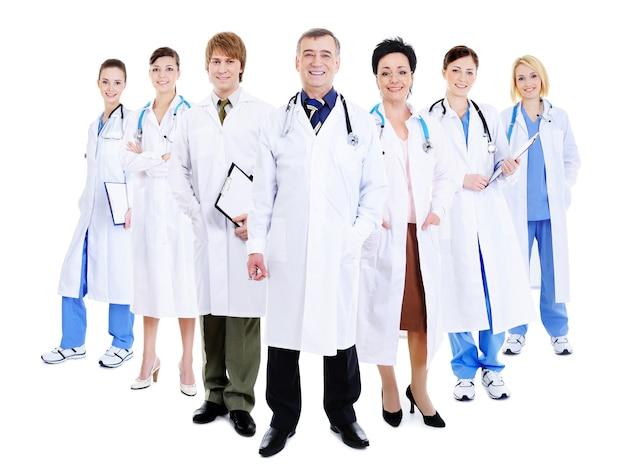 Szczęśliwy zespół odnoszących sukcesy lekarzy stojących razem w szpitalnych togach