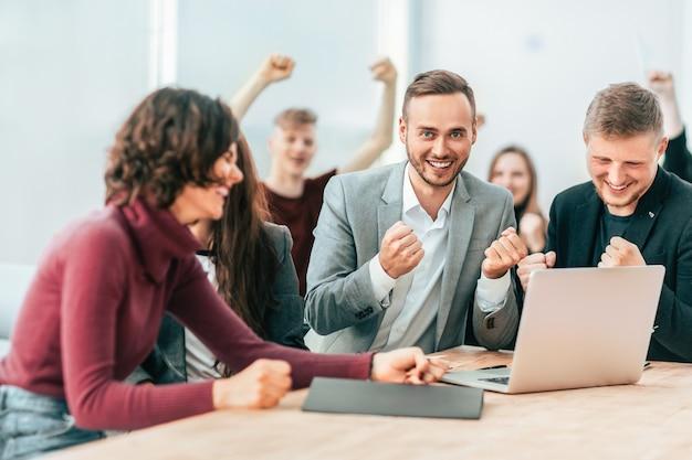 Szczęśliwy zespół pracowników patrzący na ekran laptopa