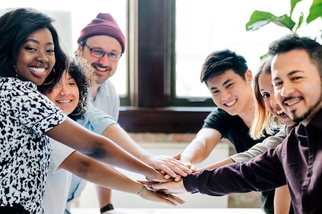 Szczęśliwy zespół składa ręce na sukces