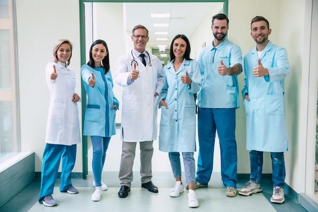 Szczęśliwy zespół udanych i pewnych siebie nowoczesnych lekarzy pozuje i patrzy w kamerę na korytarzu szpitalnym