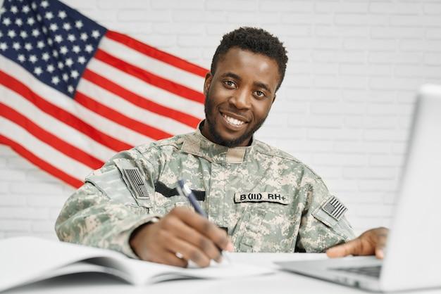 Szczęśliwy żołnierz siedzi na miejscu pracy i pisze w dokumentach.