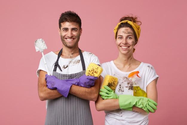 Szczęśliwy żonaty mężczyzna i kobieta noszących ubranie stojących skrzyżowanymi rękami, ciesząc się, że sprzątają swój dom, trzymając sprzęt do czyszczenia na białym tle