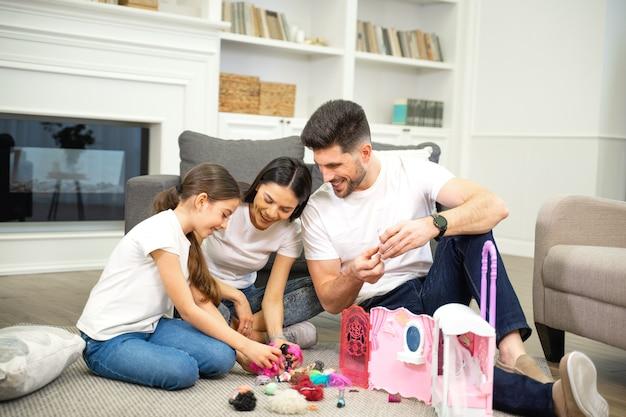 Szczęśliwy żonaty ojciec i matka bawią się z uroczą małą dziewczynką patrzącą na nowy domek dla lalek