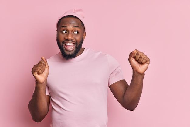 Szczęśliwy zrelaksowany mężczyzna tańczy beztrosko podnosi ramiona zaciska pięści w rytm muzyki uśmiecha się szeroko ubrany niedbale odizolowany na różowej ścianie