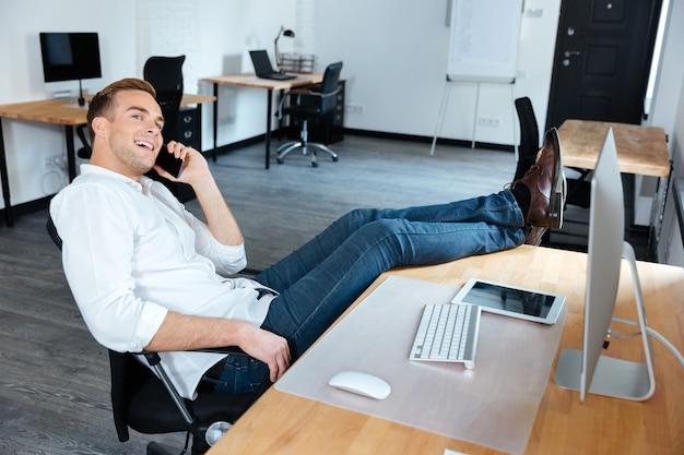 Szczęśliwy zrelaksowany młody biznesmen siedzi z nogami na stole i rozmawia przez telefon komórkowy w biurze