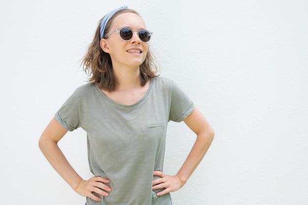 Szczęśliwy zrelaksowany żeński turysta jest ubranym okulary przeciwsłonecznych