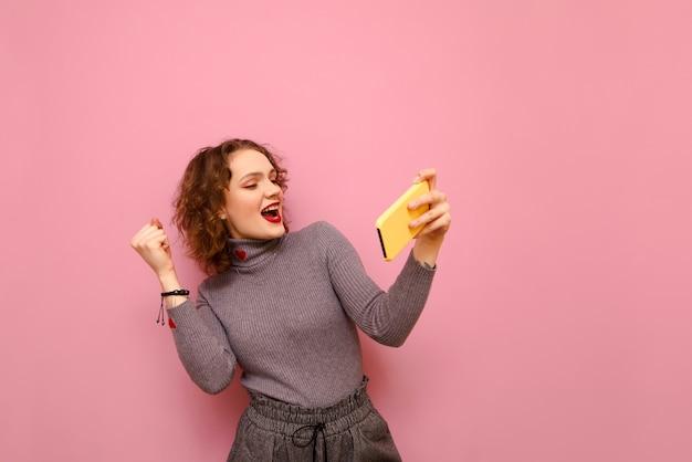 Szczęśliwy zwycięzca dziewczyna ze smartfonem w dłoniach gra w gry mobilne