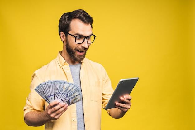 Szczęśliwy zwycięzca! młody bogacz w dorywczo trzymając pieniądze banknoty dolarowe i komputer typu tablet z niespodzianką na białym tle nad żółtym tle.